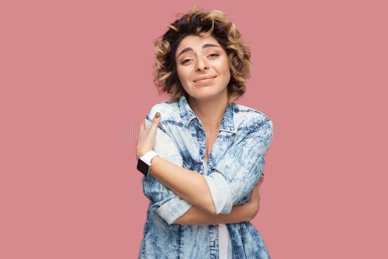 Eu amo meu auto Retrato da jovem mulher satisfeita com penteado encaracolado na posição azul ocasional da camisa, olhando a câmer foto de stock royalty free