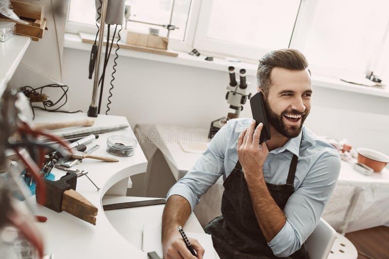 Eu amo meus clientes! O joalheiro farpado novo está falando com o cliente o telefone e pelo sorriso imagem de stock