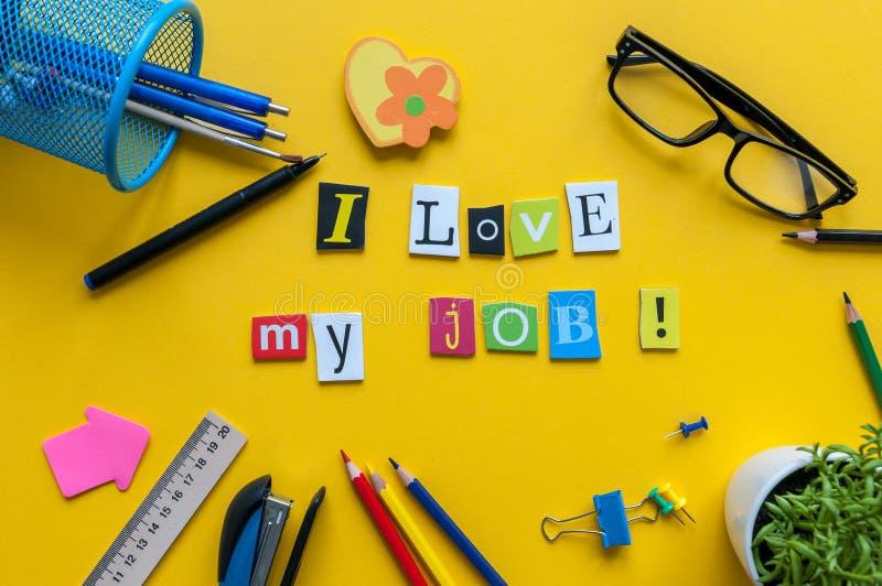 Eu amo minha palavra do trabalho escrita por letras cinzeladas no espaço de trabalho home amarelo com materiais de escritório foto de stock
