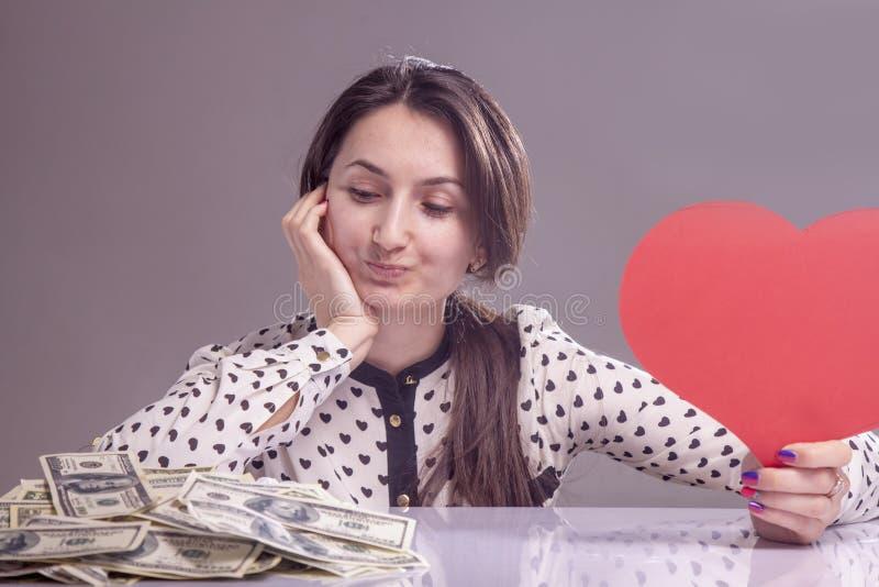 Eu amo o dinheiro! Mulher de negócio bonita que guarda o coração e o dinheiro como o símbolo do amor para dólares americanos imagens de stock