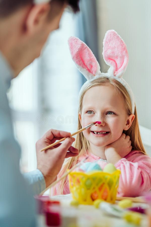 Eu amo preparar-se para a Páscoa com meu dadDad e a filha está tendo o divertimento O paizinho pinta o nariz da sua filha imagens de stock royalty free