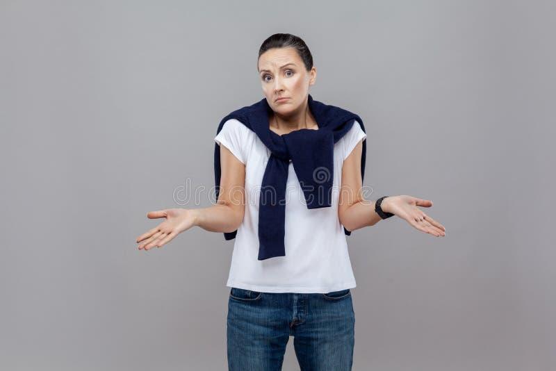 Eu don o `t sei Mulher denominada ocasional considerável com calças de ganga e s fotos de stock