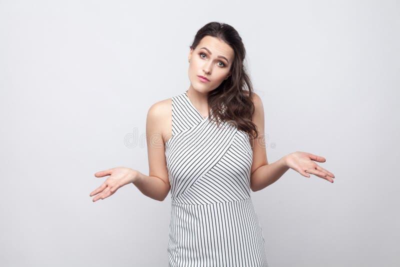 Eu don o `t sei Mulher moreno nova confusa com composição e posição listrada do vestido e vista da câmera com mãos cruzadas e imagem de stock