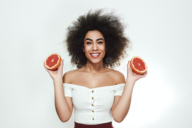 Eu escolho o alimento saudável! Mulher afro-americana bonita e alegre que guarda duas porções da toranja e que olha a câmera foto de stock royalty free