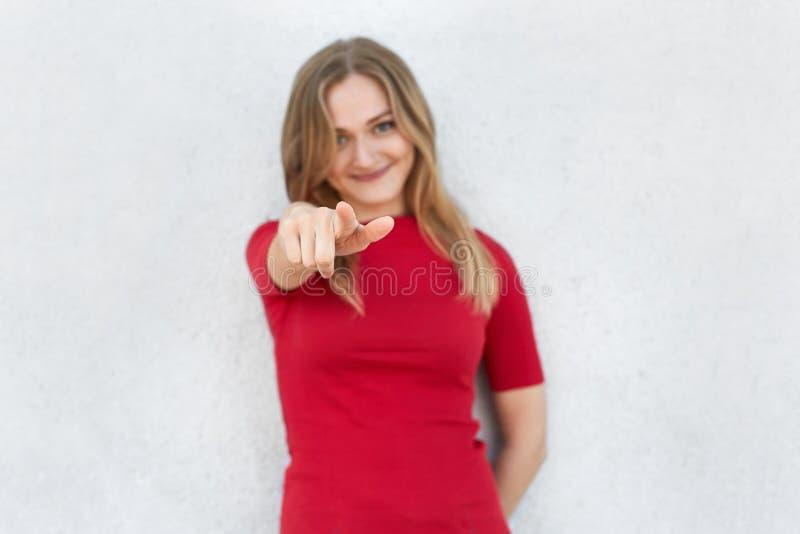 Eu escolho-o! Tiro colhido da mulher no vestido vermelho que aponta na câmera com o indicador isolado sobre o fundo branco Mulher foto de stock