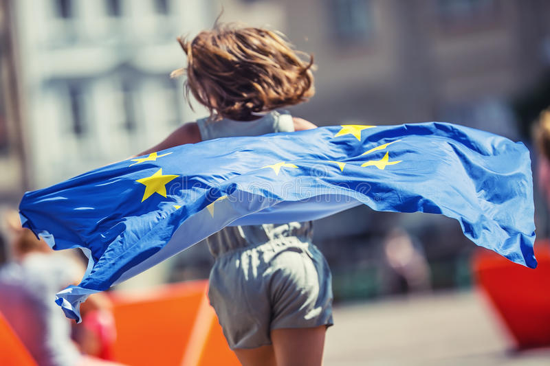 EU Flag. Cute happy girl with the flag of the European Union. Young teenage girl waving with the European Union flag in the city stock photo
