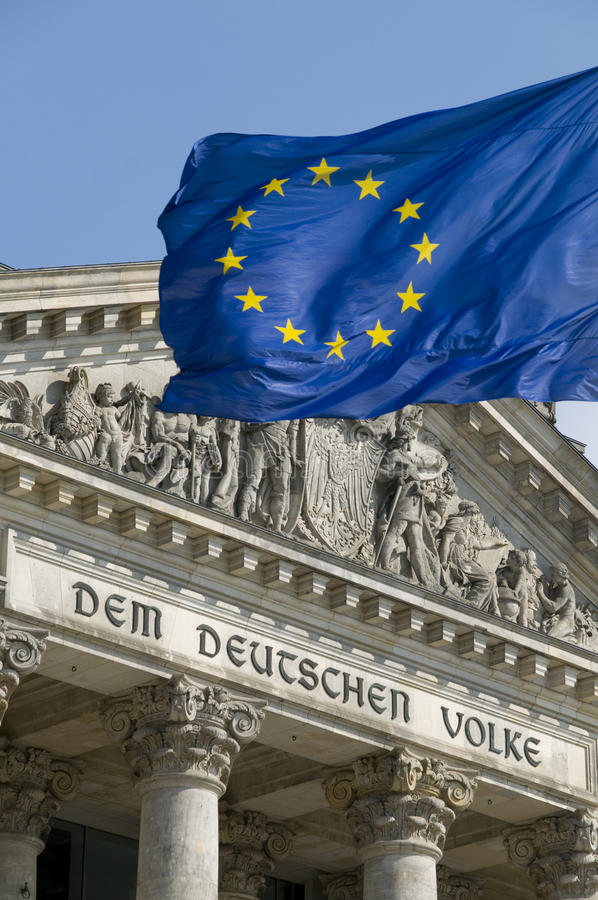 EU Flag and Reichstag. The flag of the EU flying in front of the German Reichstag in Berlin. The phrase Dem Deutschen Volke (To the German people), designed by stock photo