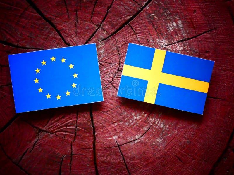 EU flag with Swedish flag on a tree stump stock photography