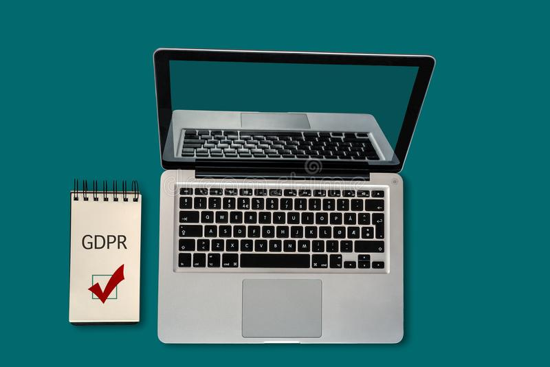 Top view of a laptop and a notepad with GDPR and a ticked checkbox on it, with copyspace. EU General Data Protection Regulation, GDPR, Concept - Rules to Comply royalty free stock image