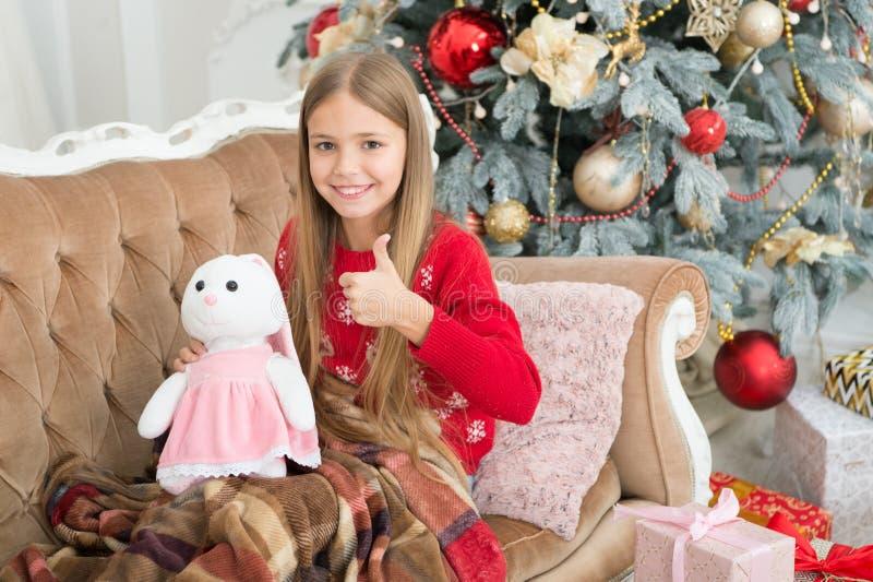 Eu gosto d muito Polegares da menina até o coelho bonito na árvore de Natal Brinquedo pequeno do coelho da posse da menina Crianç imagens de stock royalty free