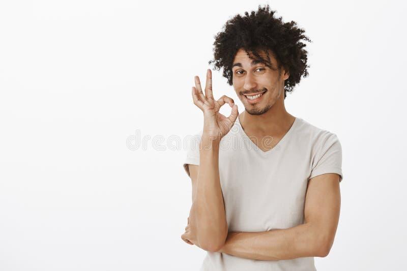 Eu obtive tudo sob o controle Homem considerável flirty satisfeito com pele escura e o corte de cabelo afro, sorrindo com encanta foto de stock royalty free
