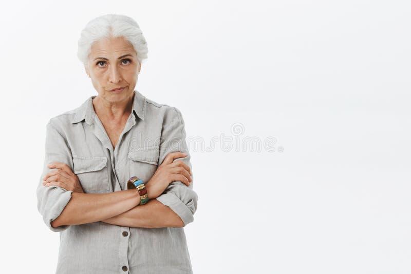 Eu preciso a jovem senhora das explicações Mãe idosa irritada desagradada com o cabelo cinzento que olha de debaixo da testa com imagem de stock