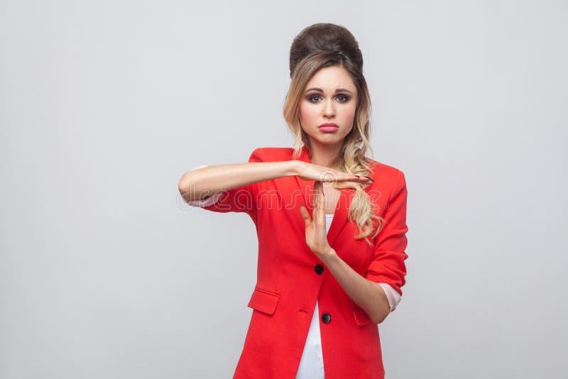 Eu preciso mais tempo Senhora bonita do negócio da preocupação com penteado e composição no blazer extravagante vermelho, estando fotografia de stock
