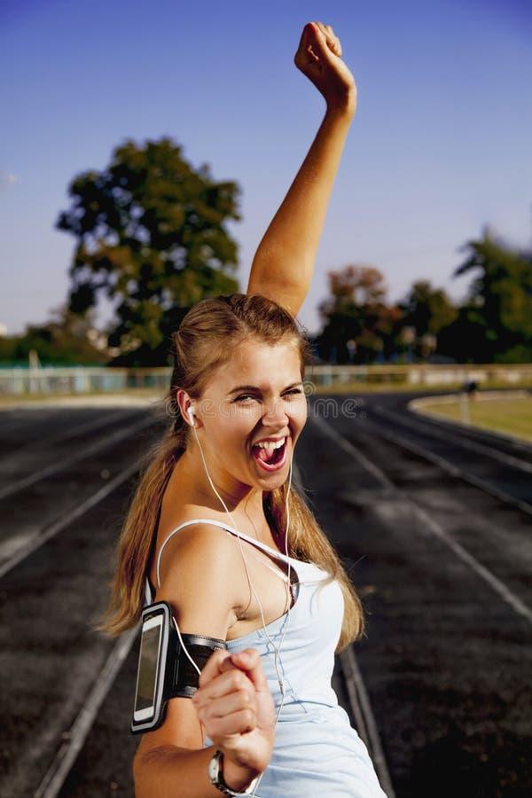 Eu sou um vencedor! Conceito saud?vel do estilo de vida Mulher feliz nova que movimenta-se na estrada de corrida fotos de stock
