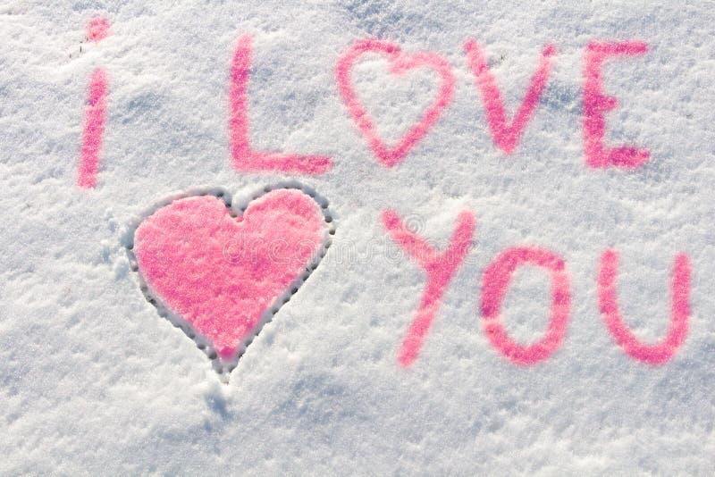 Eu te amo com escrita do sinal do coração na neve imagens de stock