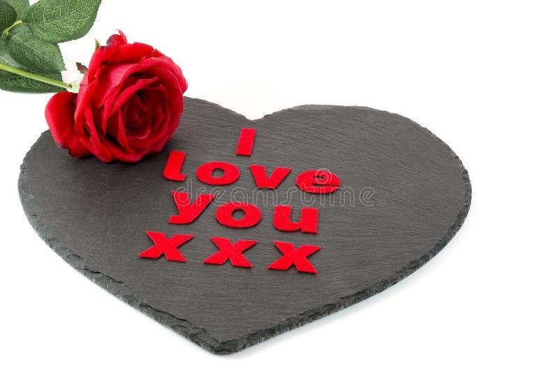 Eu te amo com uma rosa vermelha em um coração deu forma à ardósia com um branco imagens de stock royalty free