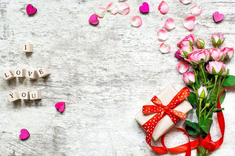 Eu te amo inscrição em cubos de madeira com o ramalhete cor-de-rosa das rosas imagem de stock
