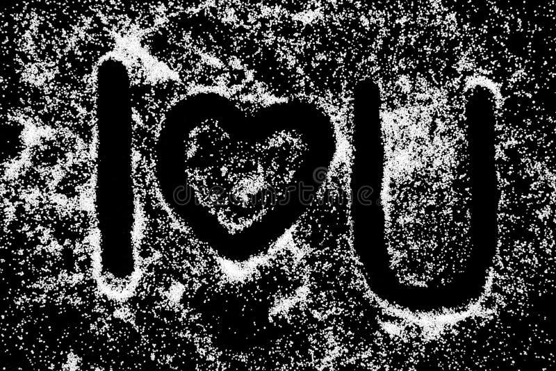 Eu te amo palavras e desenho ouvido do símbolo pelo dedo no pó branco de sal no fundo preto da placa imagem de stock royalty free