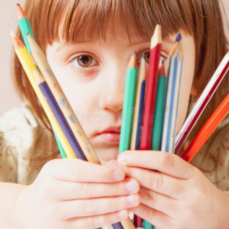 Eu ver que o mundo coloriu! Feche acima da menina bonito da criança pequena com lápis coloridos fotografia de stock