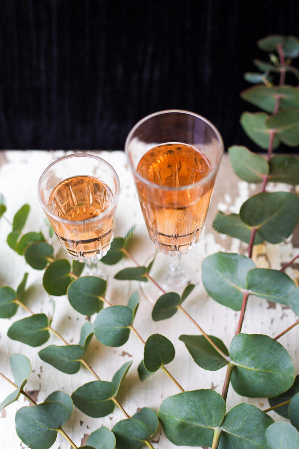 Eucalyptus branches on an old table with a glass of rose wine. Eucalyptus branches on an old table with a glass of rose wine royalty free stock photo