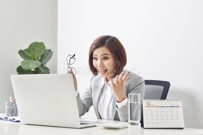 Euforische en verraste winnaar die online op laptop letten op kantoor, Mooie jonge die vrouw blij en na open e-mail wordt verrast stock afbeeldingen