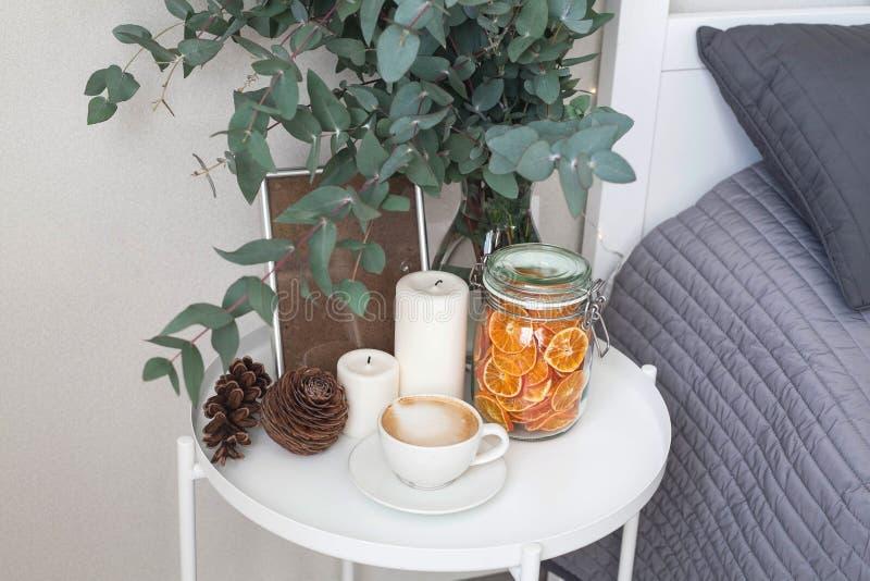 Eukalyptus im Innenraum, Morgenkaffee auf dem Tisch im Schlafzimmer durch das Bett stockbild