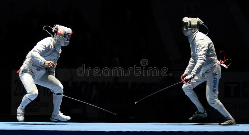 Eun Sok Oh and Luigi Samele. Eun Sok Oh (KOR) and Luigi Samele (ITA) compete at the 2010 RFF Moscow Saber World Fencing Tournament in Moscow, Russia royalty free stock photo
