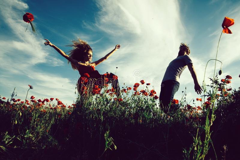 euphoria uomo e ragazza nel campo rosso del papavero fotografia stock
