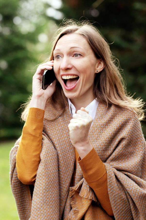 Euphoric business woman winning deal on the mobile phone. Young Business woman, international entrepreneur. After breakfast outside in the luxury hotel garden stock photos