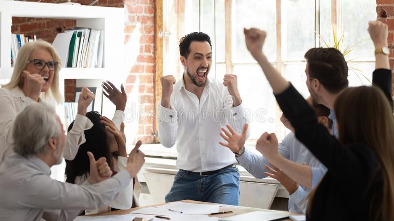 Euphoric excited business team celebrate corporate victory together in office. Happy overjoyed professionals group rejoice company victory, teamwork success royalty free stock photo
