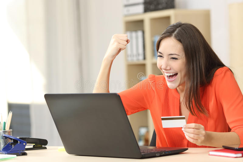 Euphoric shopper buying online. Euphoric shopper buying on line with a laptop and a credit card at home or office stock photography