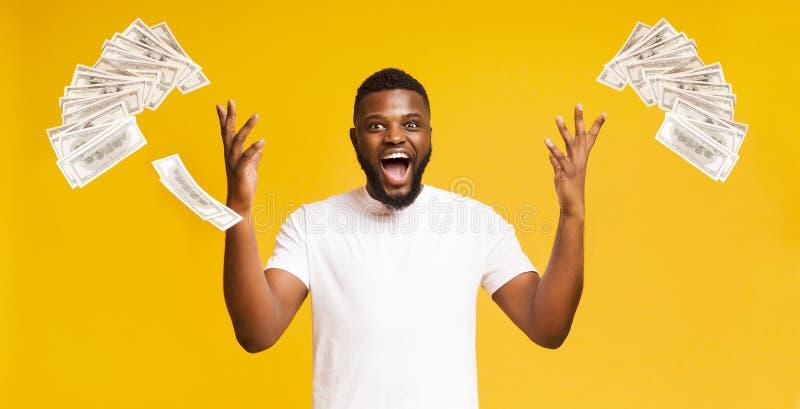 Euphoric svart man kastar upp många dollar arkivbild