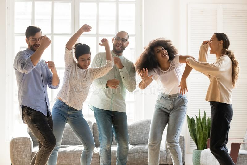 Euphoric young mixed race best friends enjoying party at home. royalty free stock image