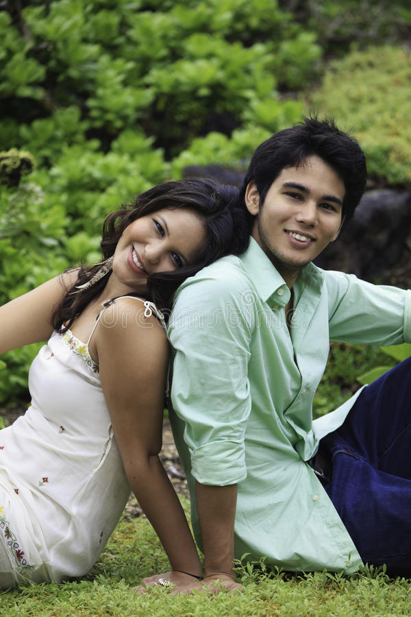 Eurasian siblings lounging. In a field in hawaii on a rainy day stock images