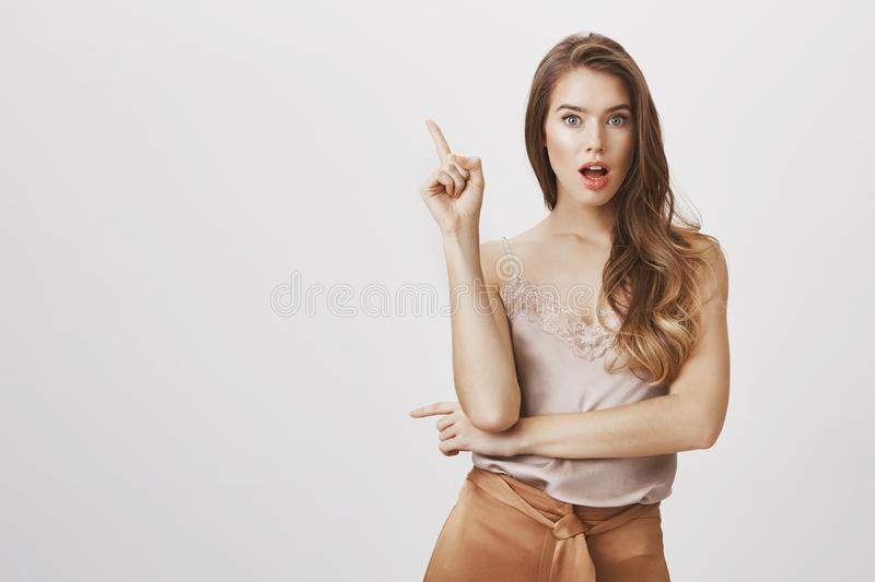 Eureka, I have great idea. Charming caucasian female in trendy outfit raising index finger and dropping jaw, remembering. Important information or making up royalty free stock image