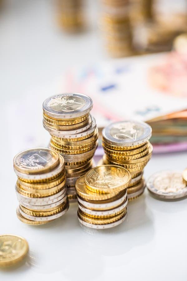 Euro bankbiljetten en muntstukken togetger op witte lijst - close-up stock fotografie