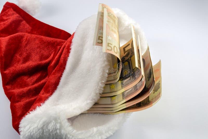 Euro bankbiljetten in Kerstman` s hoed stock foto's