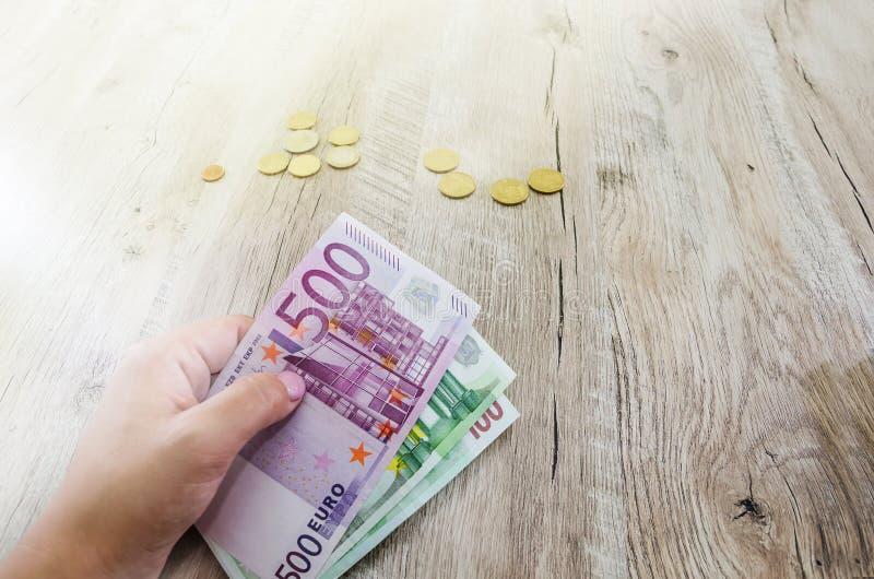 500, 100 Euro banknotów w ręce przeciw tłu monety zdjęcie royalty free