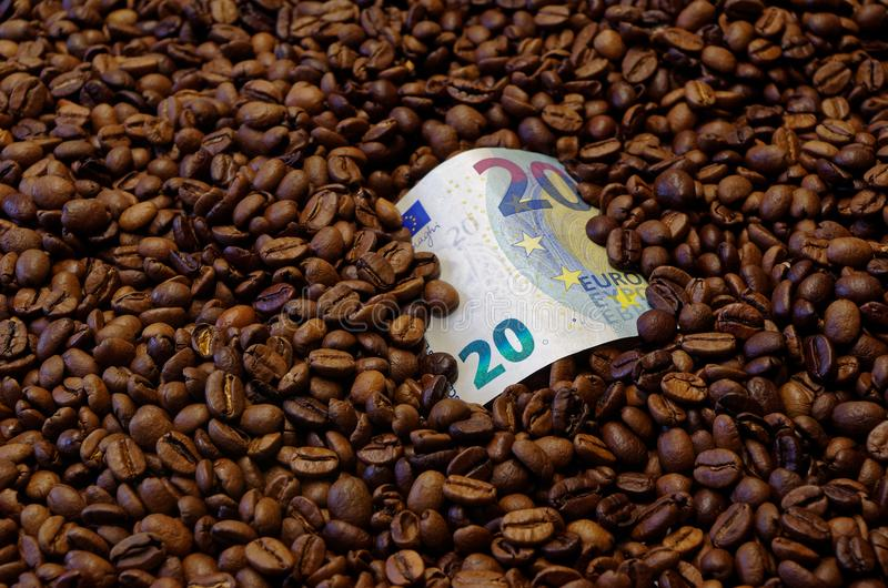 20 Euro banknote in the roasted coffee beans. 20 Euro banknote lying in the middle of roasted coffee beans royalty free stock images