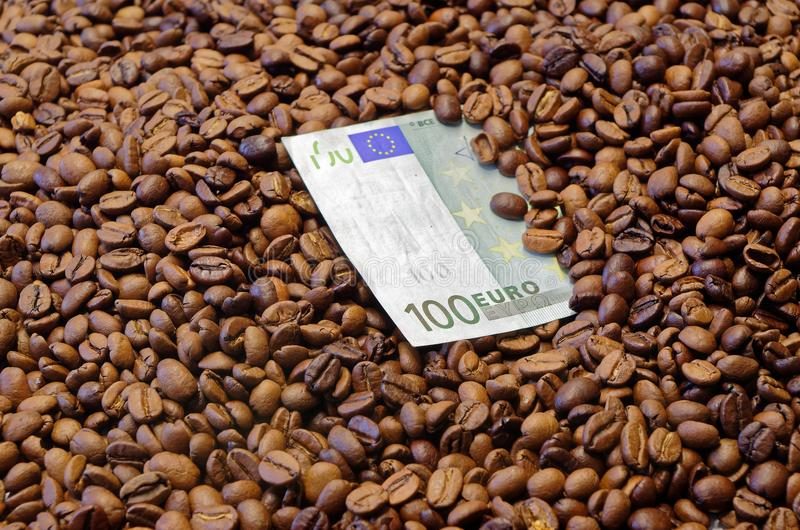 100 Euro banknote lying in the roasted coffee beans. Close up photo of one hundred Euro banknote in the roasted coffee beans stock images