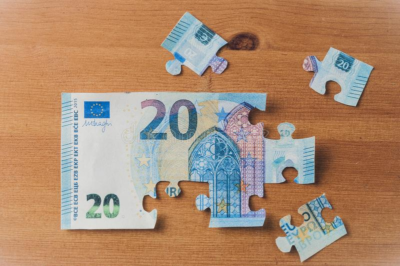 20 euro banknote puzzle. On wooden table stock photos