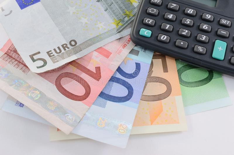 Euro banknotes and calculator. Detail of euro banknotes and calculator royalty free stock photos