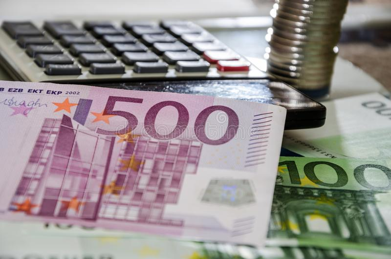 500, 100 euro banknotes, coins and calculator on a blue background. Close-up. royalty free stock image