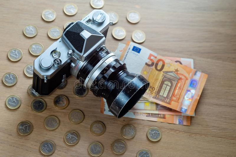 Euro banknotes, coins and a camera on a light wooden background. royalty free stock photos