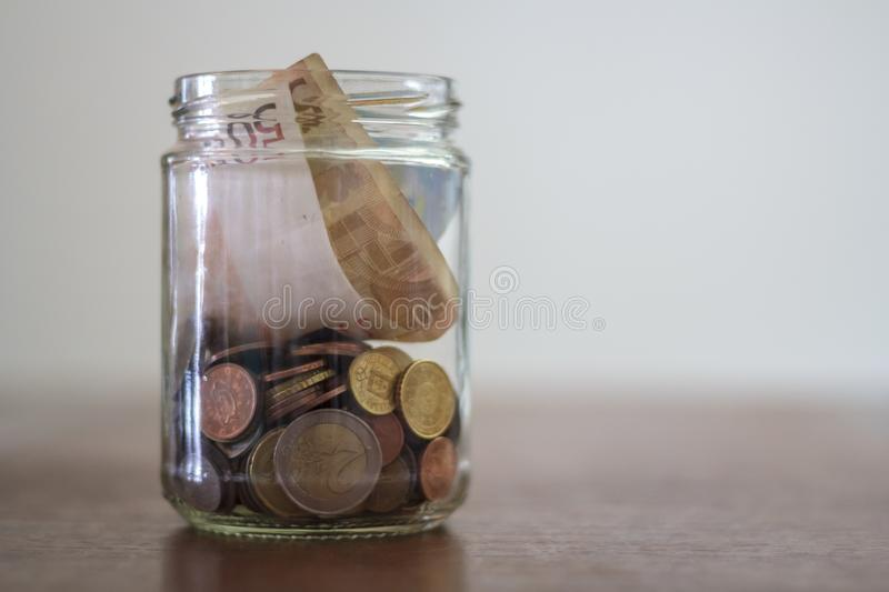 Euro Banknotes and coins in glass jar stock photo