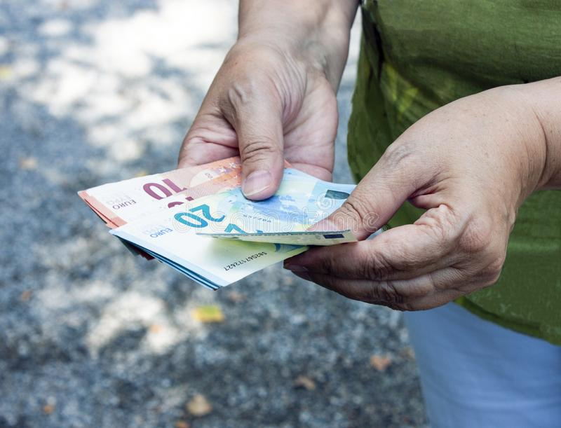 Euro banknotes in the hands. Adult woman counts money stock photography