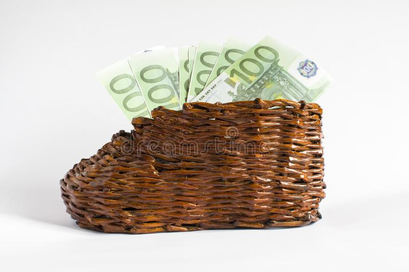 Euro banknotes lie in an old wooden boot. A denomination of the euro is in front of a wicker shoe royalty free stock image
