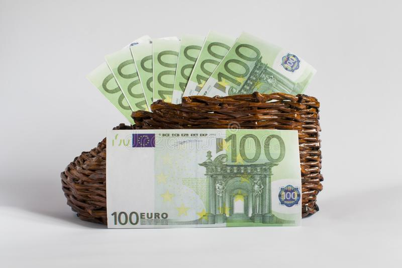 Euro banknotes lie in an old wooden boot. A denomination of the euro is in front of a wicker shoe royalty free stock photography