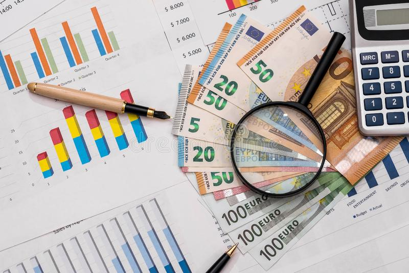 Euro banknotes with magnifier and calculator on business graphs.  royalty free stock image