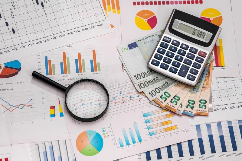Euro banknotes with magnifier and calculator on business graphs.  stock photography